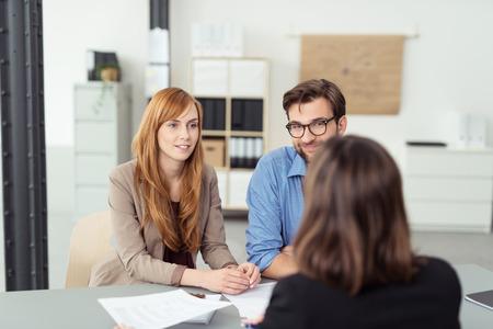 esposas: Reuni�n corredor de inversi�n con un par joven en su oficina para discutir sus necesidades financieras, vista desde detr�s de la agente de la pareja Foto de archivo