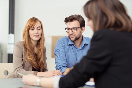 documentos legales: Broker de hacer una presentaci�n de una pareja de j�venes mostr�ndoles un documento que se est� viendo con expresiones serias