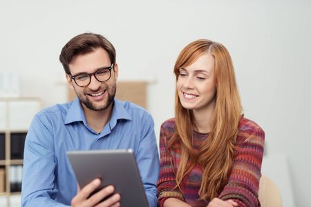 catch up: Attractive young couple smiling as they read their tablet-pc and catch up on developments in the office