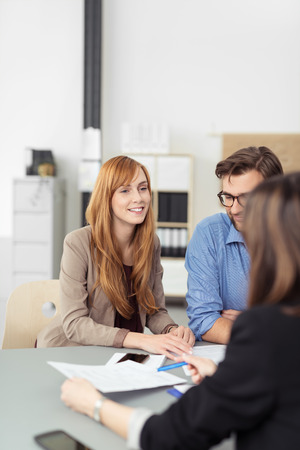 Smiling pretty redhead woman in a meeting at the office sitting at a table with her colleagues or team smiling Stock Photo