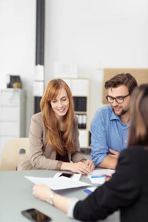 一緒に文書を見て、彼女が彼らに提示しているエージェントとの会合で座っている若いカップルをエージェントの肩越しに見る