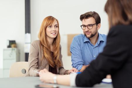 ayudando: Joven pareja casada en una reunión con un corredor o agente, con especial atención a la mujer atractiva pelirroja
