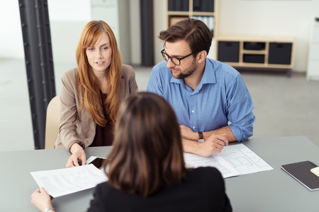 Married couple discussing investments with a broker as they sit together at a desk in her office going through paperwork together, view from behind the agent