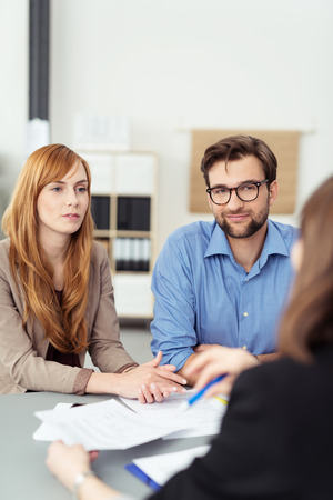 Young couple meeting with a broker or agent sitting at her desk in the office listening to te presentation with attentive expressions Foto de archivo