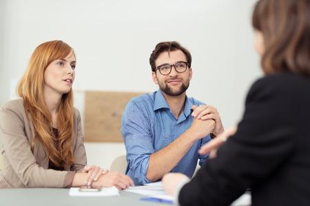 深刻な丁寧な表現で彼女を聞いて座っている若いカップルとの議論を持っている仲介商