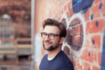 sonrisa: Retrato de hombre sonriente joven con el pelo Lentes que desgastan faciales y se inclina contra la pared de ladrillo pintada con la pintada
