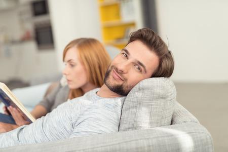 esposas: Hombre joven con el pelo facial sonr�e en la c�mara con la cabeza se recost� en el sof� del amortiguador, Relajaci�n con mujer Acurrucado Junto a �l Foto de archivo