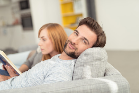 lying on couch: Young Man with Facial Hair Smiling at Camera with Head Leaned Back on Sofa Cushion, Relaxing with Woman Curled Up Beside Him
