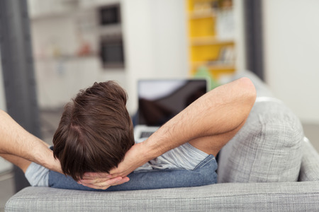 relajado: Hombre que se relaja con las manos detrás de la cabeza en el sofá y el ordenador portátil en la vuelta de salida visible de Focus en Distancia