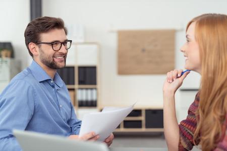amigas conversando: Compañeros de trabajo felices en la oficina papeleo discutir juntos mirando el uno al otro con sonrisas, el hombre y la mujer