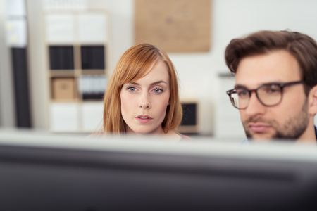 computer problem: Businesswoman and man working together at a desktop computer in the office reading the monitor with serious expressions, view to the face of the attractive redhead woman Stock Photo
