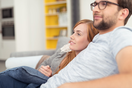 relajado: Joven pareja disfrutando de un momento de relax junto reclinables cogidos del brazo en el sofá viendo algo a la izquierda del marco, vista de cerca Foto de archivo