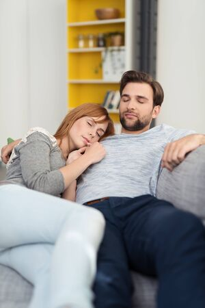 couple on couch: Young couple enjoying a relaxing nap as they sit snuggling up close on a comfortable sofa at home over the weekend