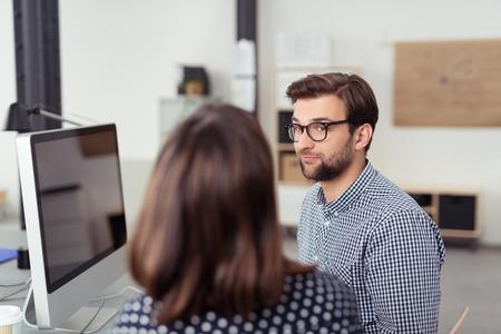 ejecutiva en oficina: Hombre hermoso con la Oficina de las lentes de escucha a su Mujer Co- Trabajador Hablando con él en su mesa de trabajo con ordenador. Foto de archivo