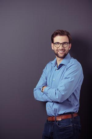 retrato: Optimista Retrato de un apuesto hombre de negocios joven de pie contra la pared gris con espacio de copia mientras mira a la cámara con armas Cruzando sobre su estómago. Foto de archivo