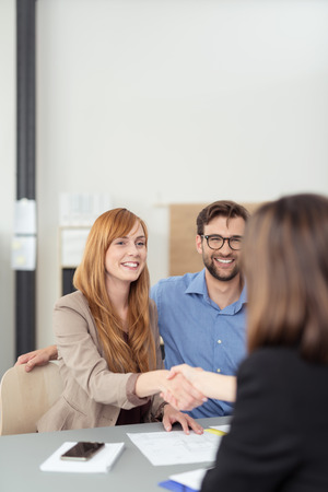 couple talking: Young couple reaching an agreement with a broker or agent as the wife shakes her hand watched by a smiling husband