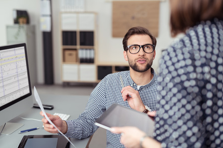 patron: Hombre joven guapo Oficina Hablando con su Gerente de Mujer Mientras sostiene un papel en su mesa de trabajo con ordenador.