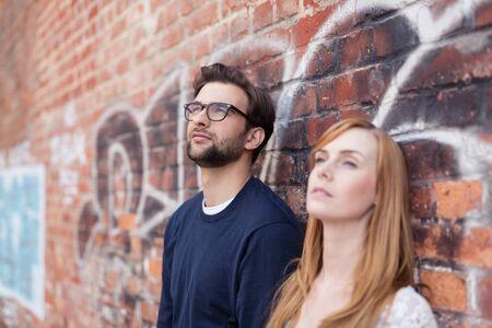 parejas sensuales: Close up Individuo Hermoso reflexiva con gafas, de pie junto a su novia, Mirar hacia arriba mientras se inclina sobre la pared de ladrillo