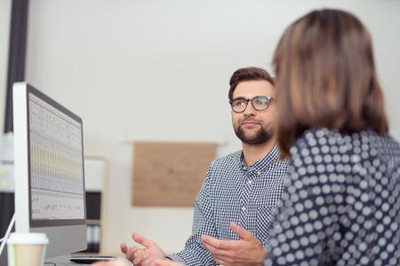 Zakenman met discussie met een vrouwelijke collega als ze zitten samen in de voorkant van een computer met zijn handen gebaren als hij iets, uitzicht over haar schouder legt Stockfoto