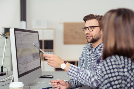 Proficient young male employee with eyeglasses and checkered shirt, explaining a business analysis displayed on the monitor of a desktop PC to his female colleague, in the interior of a modern office Archivio Fotografico