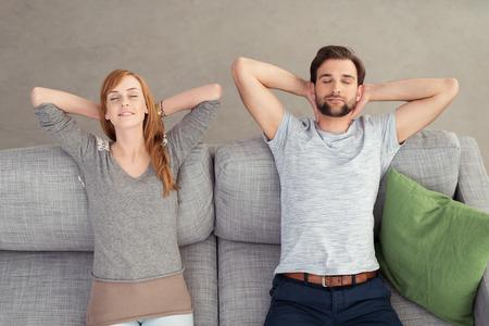 Mladý pár na dovolené na šedé gauč s rukama na zadní straně jejich hlav a oči zavřené. Zachyceny v vysokého úhlu pohledu