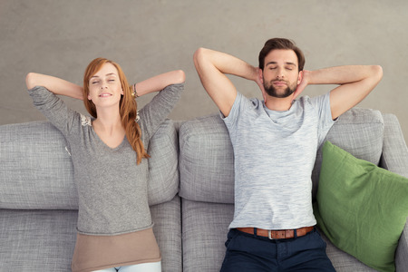 couple on couch: Young Couple Relaxing on Gray Couch with Hands On the Back of their Heads and Eyes Closed. Captured in High Angle View Stock Photo