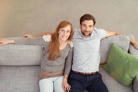 couple couch: Smiling Sweet Young Couple Sitting on Gray Couch, Looking at the Camera in a High Angle View.