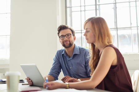 Dois jovens empresários sentado à mesa com computador portátil dentro do escritório.