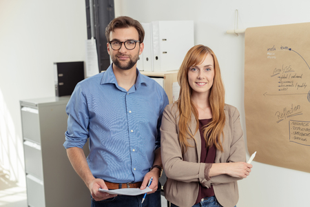 professional man: Half Body Shot of a Confident Young Professional Couple Standing Inside the Office and Smiling at the Camera.
