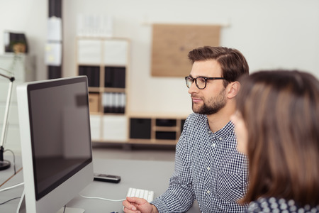 edv: Two young employees, man and woman, staring at a turned off PC monitor while sitting at desk in the interior of an office with modern equipment Stock Photo