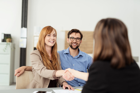 business  deal: Happy young couple meeting with a broker in her office leaning over the desk to shake hands, view from behind the female agent Stock Photo