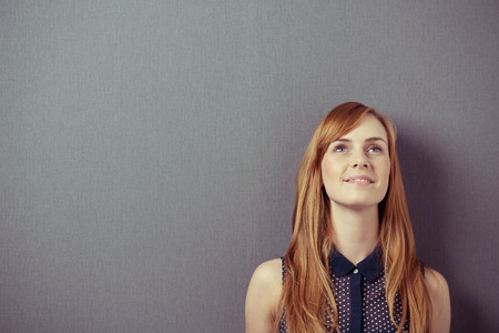 Young redhead pretty woman wearing a sleeveless shirt while smiling and looking up with a positive attitude, planning or anticipating a great future, portrait with copy space on grey