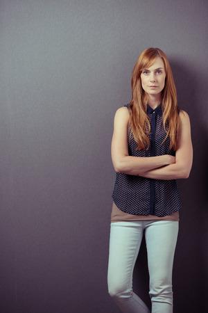 tight jeans: Seria mujer pelirroja de pelo largo joven con ropa casual pantalones de mezclilla tan ajustados y camisa sin mangas con estampado de flores mientras est� de pie con los brazos cruzados y apoyado contra una pared gris Foto de archivo