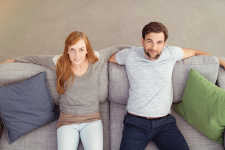 couple on couch: Young Couple Sitting on the Gray Living Room Couch with Wide Open Arms and Looking at the Camera. Captured in High Angle View. Stock Photo