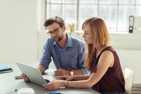 ayudando: Pares que trabajan juntos en una oficina sentado en una computadora port�til de leer la pantalla con expresiones serias Foto de archivo