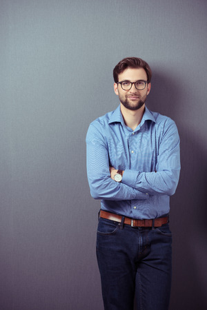 standing against: Confident bearded young man wearing brown leather belt, wristwatch, eyeglasses and blue jeans and casual shirt while standing with folded arms and leaning against a grey wall