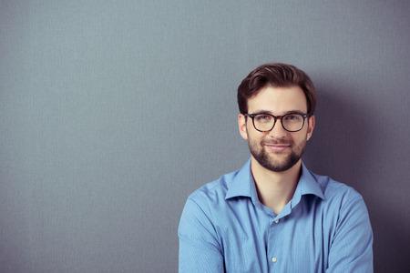 portrét: Zblízka usmívající se mladý podnikatel nosí brýle, při pohledu na fotoaparát proti šedé zdi pozadí s kopií prostor