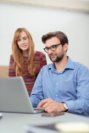 edv: Smiling Young Male and Female Business Partners Watching Something at the Laptop Screen Together While at the Office