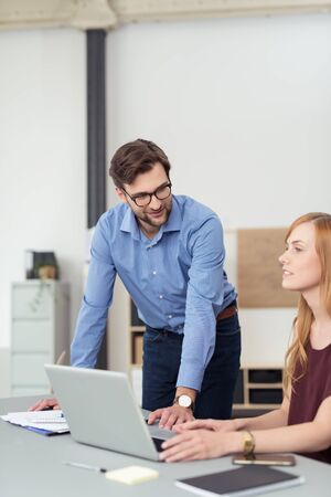 edv: Young bearded businessman wearing glasses standing helping a female colleague as he leans over her desk Stock Photo