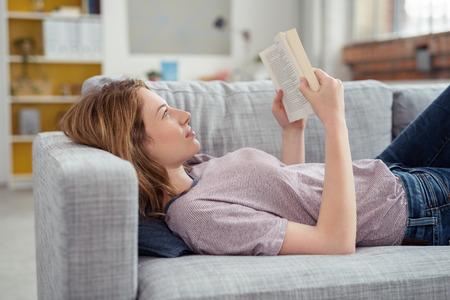 descansando: Perfil de joven Morena mujer relajante en el sofá y la Lectura de Novela libro en casa