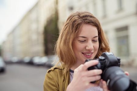 都会の屋外でデジタル一眼レフ カメラの背面ディスプレイを見て笑顔の若い女性のクローズ アップ