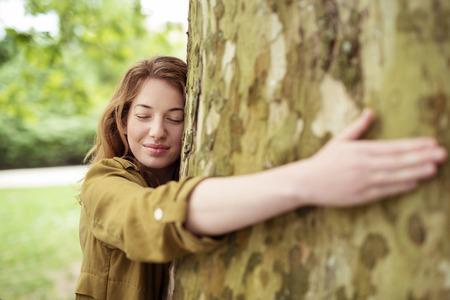 personas abrazadas: Adolescente rubio pensativo Muchacha que abraza el enorme tronco de árbol en el parque con los ojos cerrados y el rostro sonriente. Foto de archivo