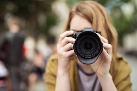 facing to camera: Close up Blond Teen Girl at the Street Holding a DSLR Camera, Taking Photo While Facing at the Camera