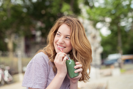 teens: Close up Cheerful Blond Teen Girl Holding a Bottle of Green Juice, Looking Up at her Back While Thinking of Something Good.