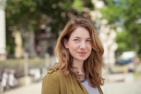 femmes souriantes: Close up réfléchie Jolie Ado fille blonde à la rue à la recherche en distance avec un visage souriant. Banque d'images