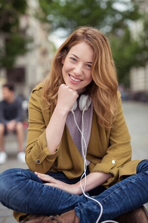legs around: Pretty Blond Girl with Headphone Around her Neck, Sitting on Bench with Legs Crossed and Chin Resting on Hand While Smiling at the Camera.