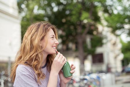 resfriado: Feliz chica rubia sentada en el parque, bebiendo una botella de jugo verde fr�a mientras que sonr�e en la distancia.