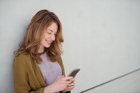 smiling girls: Half Body Shot of a Pretty Smiling Girl in Casual Wear, Busy Using her Mobile Phone While Leaning on the White Wall. Stock Photo