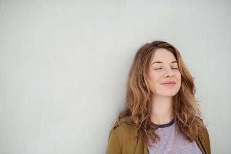 Close up premurosa sorridente ragazza bionda Chiudendo gli occhi, mentre appoggiandosi su un muro bianco con Copia spaziale