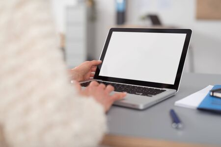 blank screen: Close up Office Woman Using her Laptop Computer on the Table with Blank White Screen, Emphasizing Copy Space.